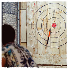 A man follows through with throwing an axe at this Indianapolis axe throwing facility.